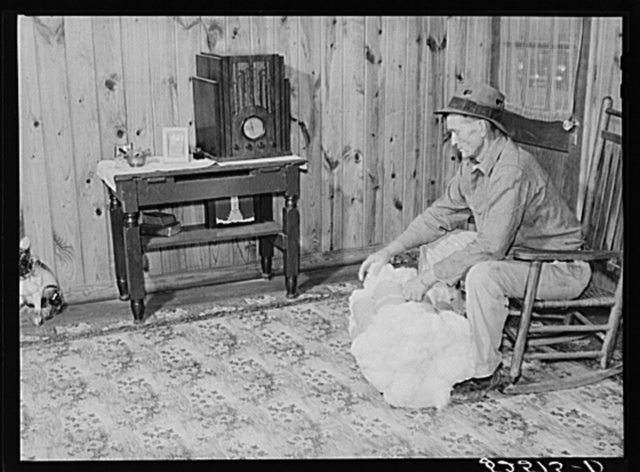 Project farmer with his cotton samples in the living room of his new home. Sunflower Plantations, Merigold, Mississippi Delta