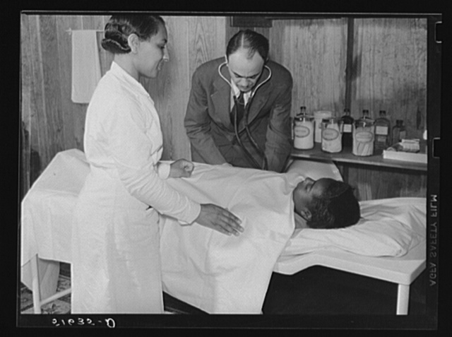 Project nurse Lillie Mae McCormick assists Dr. Thomas M. Adams as he takes Annie Maude Daniels' blood pressure on table in health clinic. Flint River Farms, Georgia