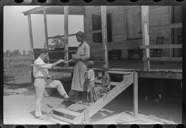Public health doctor giving tenant family medicine for malaria, near Columbia, South Carolina