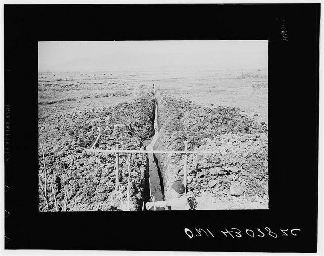 Public Health Serive Investigation Commission to the China-Burma higway, Chefang Valley, China. Long straight ditch the morning after it had been dug. The soil is so soft that the walls shift in one night whenever there is action by small springs