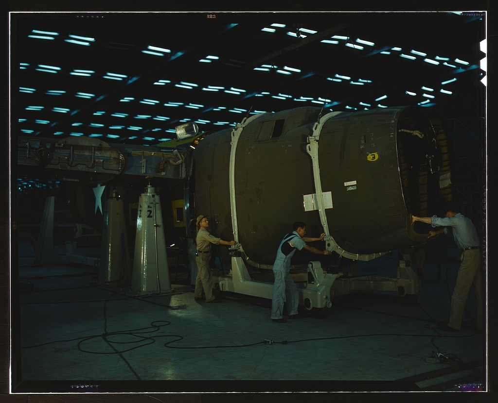 Putting the nose section of a mighty transport plane in place in the fuselage mating fixture at the Consolidated Aircraft Corporation plant, Fort Worth, Texas