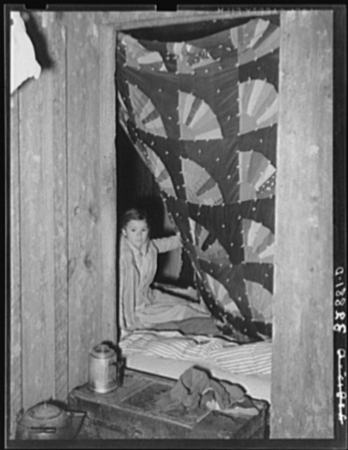 Quilt hung across doorway which separates living quarters of two families of white migrants. Berry pickers near Hammond Louisiana