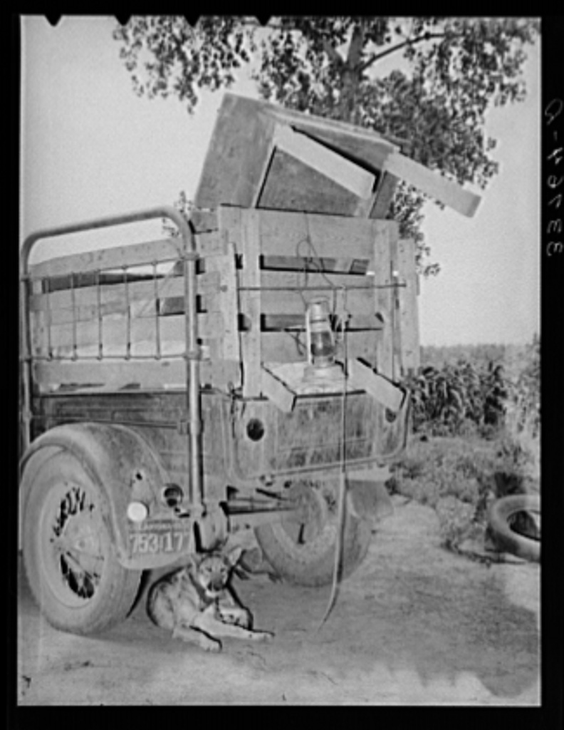 Rear of migrant's truck with dog underneath it. Getting ready to leave for California. Near Muskogee, Oklahoma
