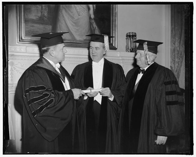 Receive honorary degrees. Washington, D.C., Feb. 23. Dr. Oswaldo Aranha, center, Brazilian Foreign Minister, receiving from Dr. Cloyd Heck Marvin, left, President of George Washington University, and honorary degree of Doctor of Laws at graduation exercises. On the right is American Ambassador from the U.S. to China, Nelson Johnson, who received a citation, 2-23-39