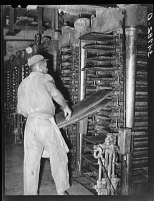 Removing the cotton seed cake and mat from hydraulic presses after the oil has been removed. Cotton seed oil mill, McLennan County, Texas