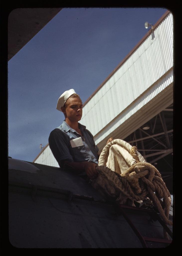 Sailor mechanic inspecting a PBY plane at the Naval Air Base, Corpus Christi, Texas