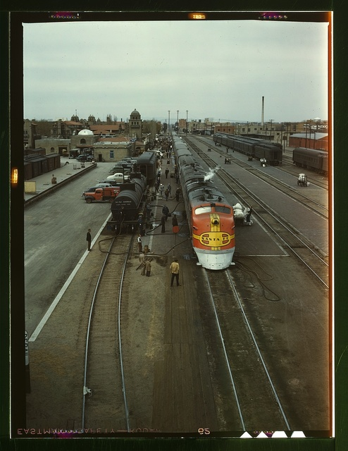 "Santa Fe R.R. streamliner, the ""Super Chief,"" being serviced at the depot, Albuquerque, N[ew] Mex[ico]. Servicing these diesel streamliners takes five minutes"