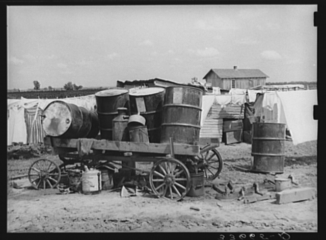 Scene on a tractor farm. Trailer loaded with oil drums. In Arkansas River bottoms near Vian, Oklahoma. Former tenant farmer is now day laborer