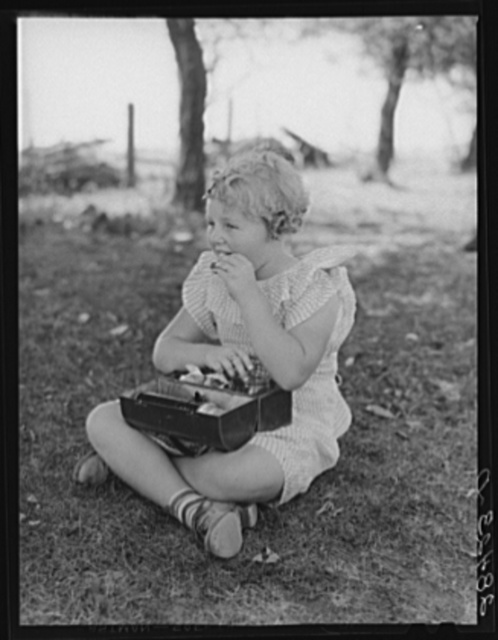 Schoolgirl, pupil of one-room schoolhouse, eating lunch. Grundy County, Iowa