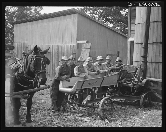 Seven of the eight farmers shown with their cooperatively owned ensilage cutter on the Miller farm, where they are working filling the silo. Yamhill County, Oregon. General caption number 58