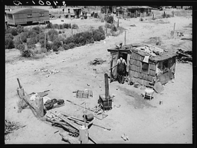 Shack home and yard. Mays Avenue camp, Oklahoma City, Oklahoma. Notice crude fence made of old water boilers and discarded fencing. See general caption no. 21