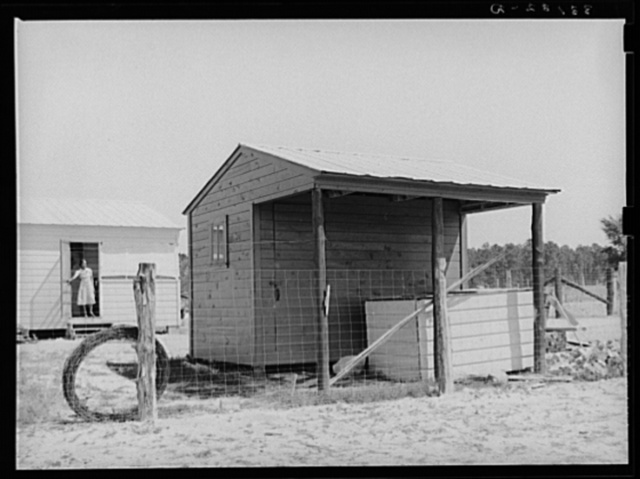 Shed and corner of house on farm unit. Sabine Farms, Marshall, Texas