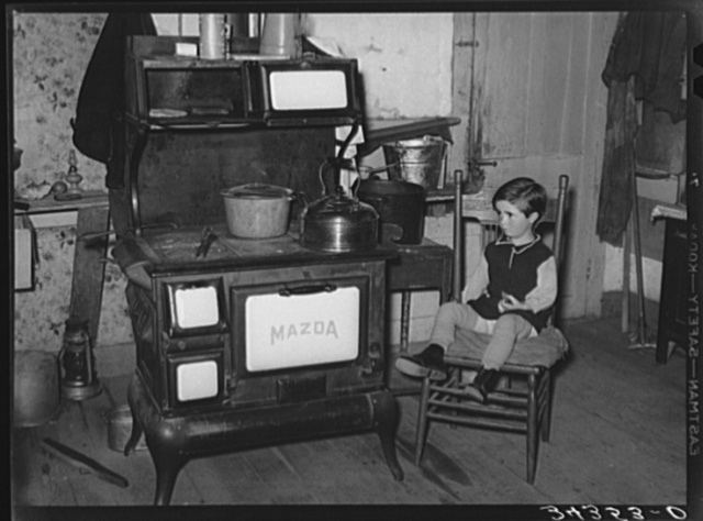 Sitting by the kitchen stove on a cold autumn day in New England. Near Bradford, Vermont, Orange County