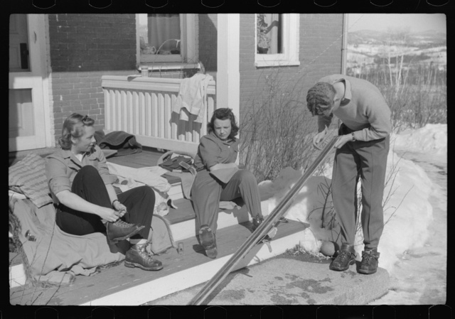 Skiers on porch of Mr. Dickinson's home in Lisbon, Franconia, New Hampshire. He installed a ski tow on his property three years ago costing around one thousand dollars, and this is the first year he has made any money on it, but business is increasing rapidly now. He has a small dairy farm and until the hurricane last year destroyed his entire grove of maple trees, he made and sold maple syrup