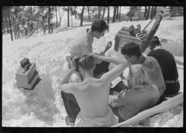 Skiers relaxing in the sun during noon hour outside of forest ranger's hut near the top of Mount Mansfield, Smuggler's Notch, near Stowe, Vermont