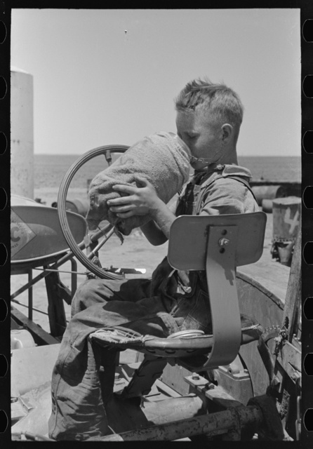 Son of day laborer on farm near Ralls, Texas. He is drinking from the jug which is carried on his father's tractor