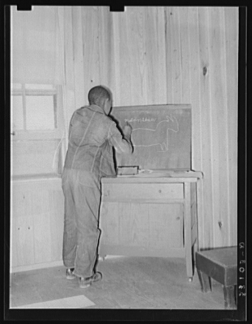 Son of FSA (Farm Security Administration) client writing name and drawing picture of mule on blackboard in his home. Sabine Farms, Marshall, Texas
