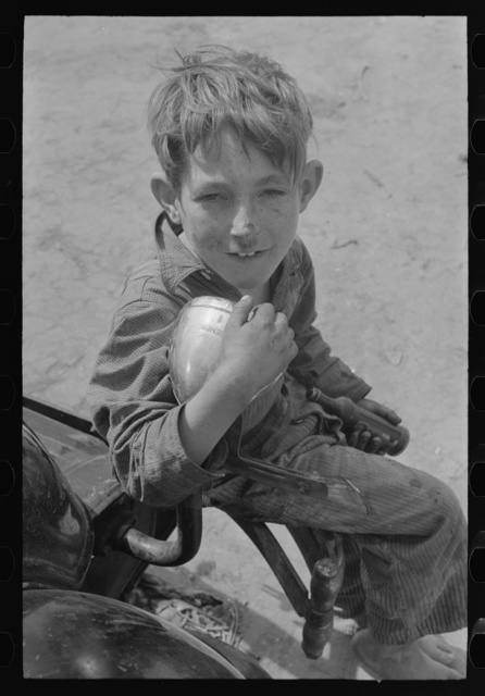 Son of migrant sitting on rear bumper of automobile, north of Harlingen, Texas