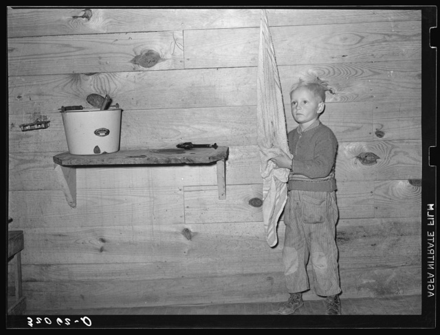 Son of tenant farmer washing hands. Near Pace, Mississippi. Background photo, Sunflower Plantation