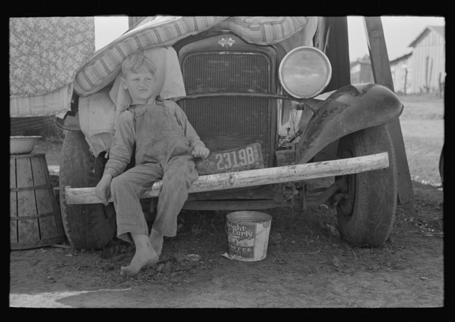 Son of white migrant sitting on bumper of their truck, Weslaco, Texas. Notice New Mexico license