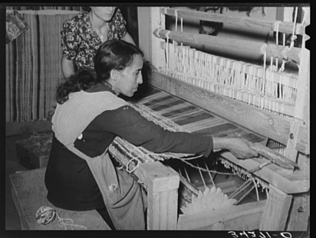 Spanish-American woman passing shuttle through warp in weaving rag rug. WPA (Works Progress Administration/Work Projects Administration) project. Costilla, New Mexico