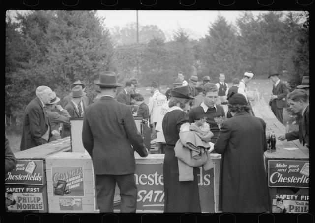 Spectators at refreshment stand during the halves of the Duke University-North Carolina football game. Durham, North Carolina