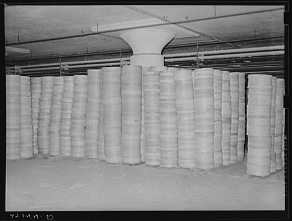 """Stacks of cheese in cold storage warehouse, Jersey City, New Jersey, in """"cooler room"""""""