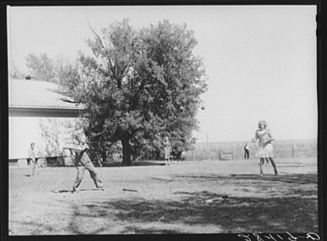 Teacher supervises ball game during recess period. Grundy County, Iowa