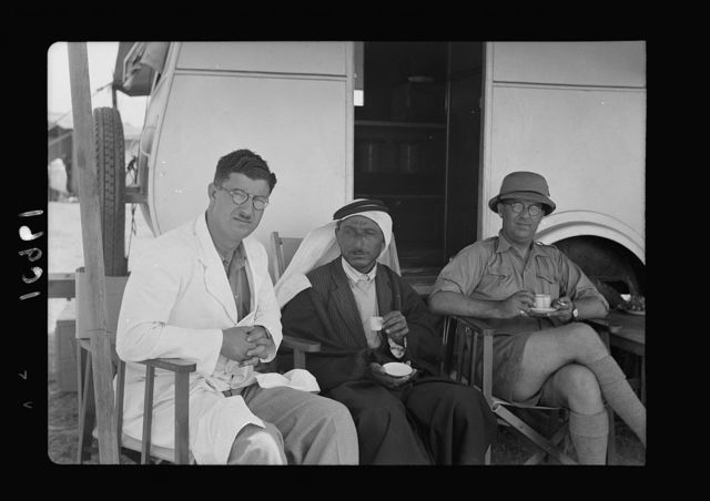 The Dept. of Health, Mobile Ophthalmic Clinic. Operating in Arab villages of the South Country, N.E. of Gaza. Left to right: Dr. Shukeir, the Mukhtar of Nedjd village & Dr. V. L. Ferguson taking coffee in shade of van
