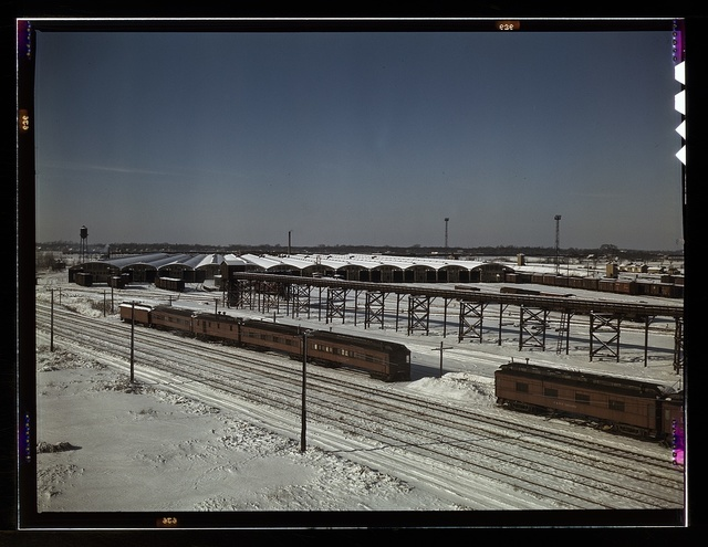 The freight house at a Chicago and Northwestern Railroad yard. In the foreground are old cars used as living quarters for some yard workers and itinerant help; Chicago, Ill.