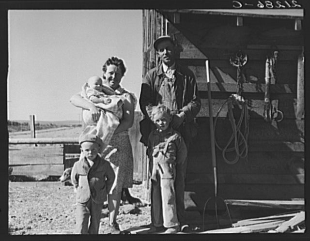 The Schroeder family on their new farm. When they first came two years ago lived in shed shown. Dead Ox Flat, Malheur County, Oregon