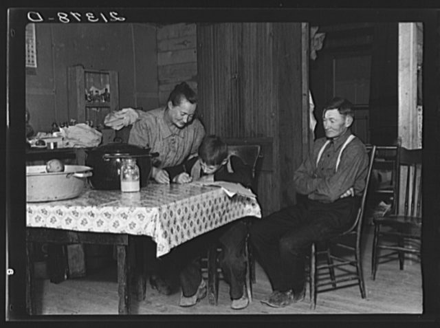 The Wardlow family in their dugout basement home on Sunday. The youngest boy copies out a recipe for his mother. Dead Ox Flat, Malheur County, Oregon