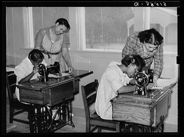 Thelma Shamburg and Mrs. Spragg (or Sprague), NYA (National Youth Administration) state supervisor, helping Catherine Plumer and Sallie Titus at sewing machines in school economics room. Gee's Bend, Alabama