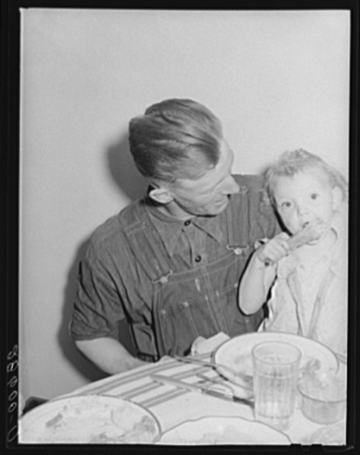 Thomas Beede and small daughter at the dinner table in their home. Western Slope Farms, Colorado
