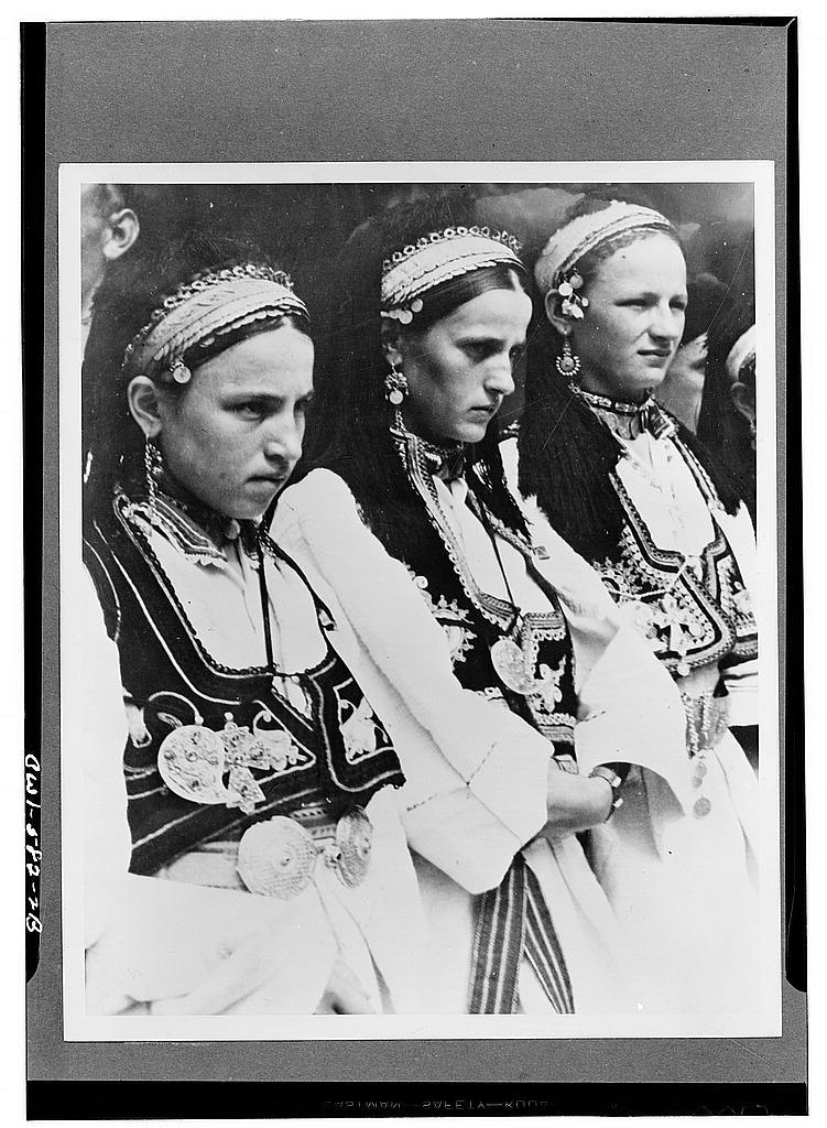Three girls in national costumes from southern Serbia, the cradle of the great Serb state in the Middle Ages. They typify the purest element conserved in the Serb race
