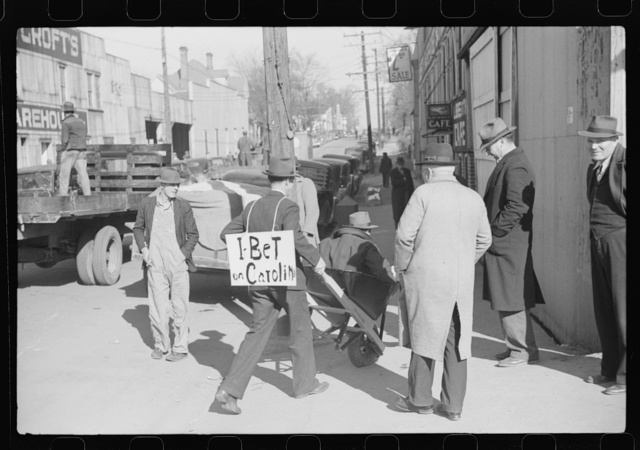 """Tobacco auctioneer who """"bet on Carolina"""" and lost, pays off the wager by pushing the warehouseman in a wheelbarrow from the warehouse to the courthouse. Durham, North Carolina"""