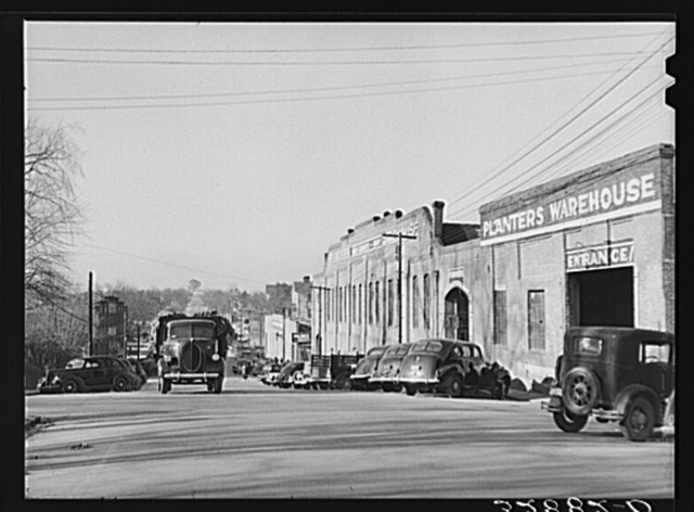 Tobacco warehouses on main street of South Boston, Halifax County, Virginia. A truck is hauling a load of tobacco after the auction. There are eleven warehouses in this small town