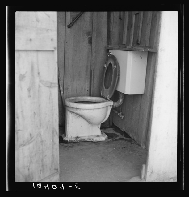 Toilet for ten cabins, men, women and children in auto camp for Arkansawyers, recent migrants to California. Rent for cabins ten dollars a month. Greenfield, Salinas Valley, California