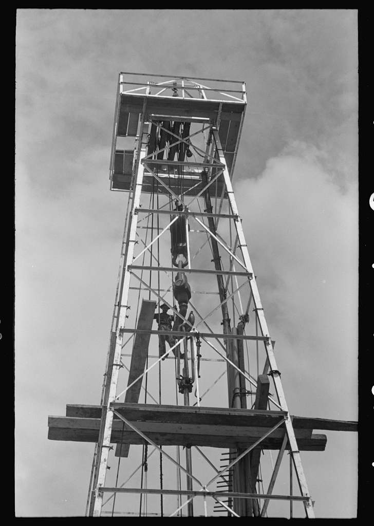 Top of derrick showing gin pole, crow's nest, crown block, traveling block, elevator and cat line. Oil well, Kilgore, Texas