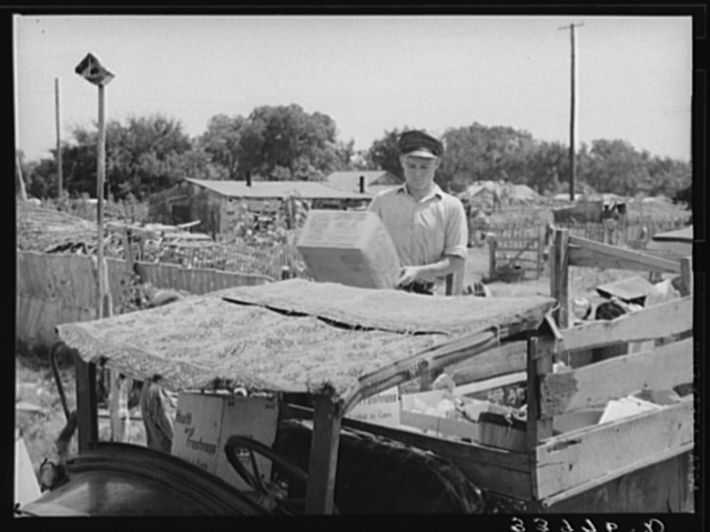 Top of oil truck made of old carpets. Boy is unloading discarded crates and overripe vegetables which he found in city market. Oklahoma City, Oklahoma. See general caption no. 21