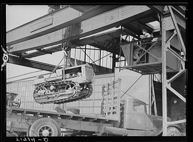 Tractor, transported by truck to FSA (Farm Security Administration) warehouse depot for repairs, being hoisted by Shepard crane to shop inside. Atlanta, Georgia