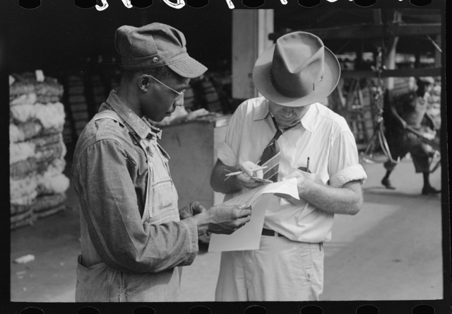 Trucker and weighing checker at unloading platform. Cotton compress, Houston, Texas