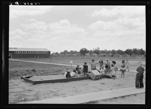 Tulare County, California. Farm Security Administration (FSA) camp for migratory agricultural workers. Nursery school children with their teacher, who is assigned to the camp by Works Progress Administration (WPA). Steel shelters in background
