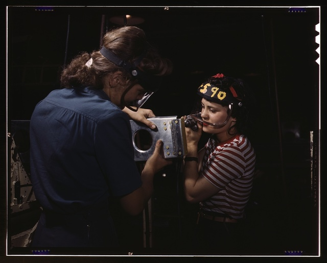Two women employees of North American Aviation, Incorporated, assembling a section of a wing for a P-51 fighter plane