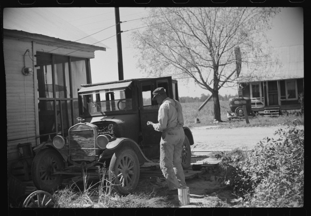 Uncle George who has worked on Marcella Plantation in blacksmith and carpentry shop for last fifty years after he got out of prison, fixing his old car, Mileston, Mississippi Delta, Mississippi