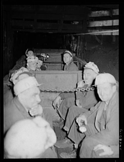 "Underground at Old Ben number eight mine. These men are on a ""man-trip"" which goes three and half miles to the face of the coal. General caption: Most of the giant coal producers in Franklin Couny have completely mechanized underground operations. Old Ben number eight, because of shortage of working capital, has not been able to install loading machines to handle the entire output of the mine. Accordingly, the mine still uses the now obsolete pit car loader, and even employs a few hand loaders alongside modern, highly efficient automatic loading machines"