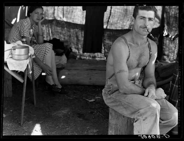 Unemployed lumber worker goes with his wife to the bean harvest. Note social security number tattooed on his arm. Oregon. See general caption number 46