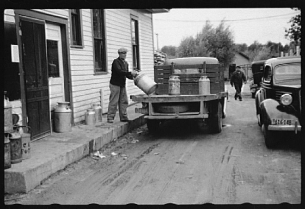 Unloading milk cans at cooperative creamery which has received a loan from the FSA (Farm Security Administration), Coleraine, Minnesota