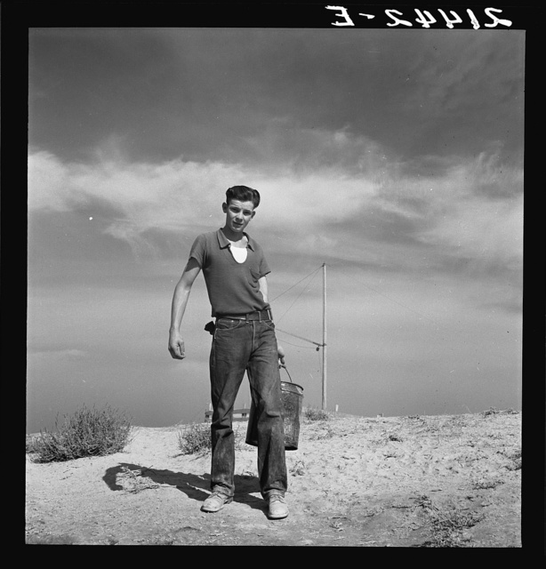 Vale Owyhee irrigation project. Seventeen year old boy going to feed the pigs. Homedale district, Malheur County, Oregon