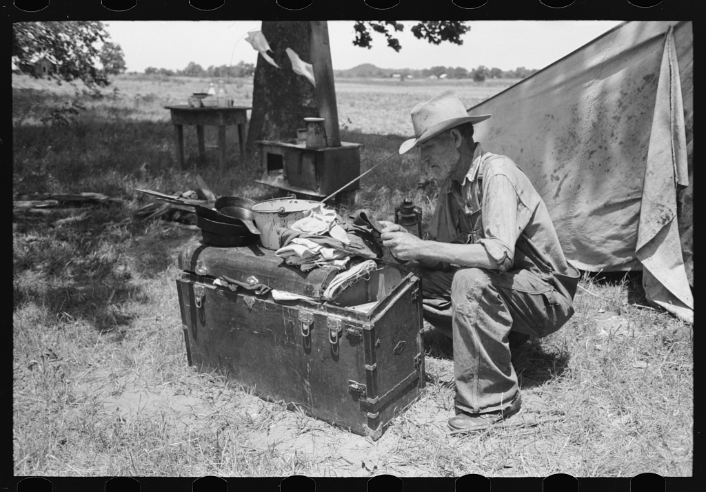Veteran migrant agricultural worker examining contents of his trunk, camped on Arkansas River in Wagoner County, Oklahoma
